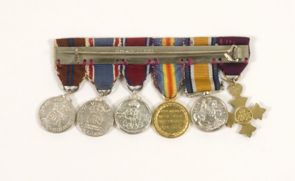 Image: six medals and ribbons aligned and seen from reverse side.