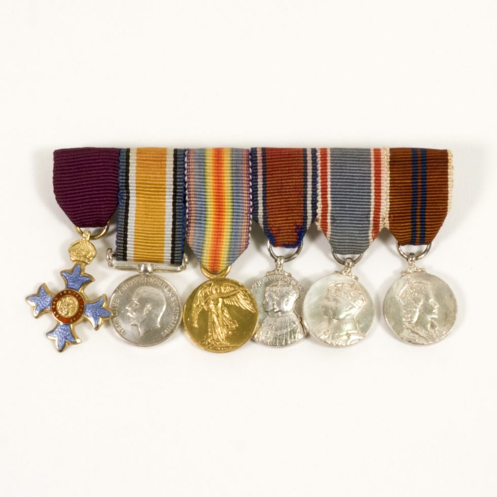 Image: 6 medals and ribbons aligned. Five of the six are circular and the sixth is a cross with a circular middle and a crown on top.