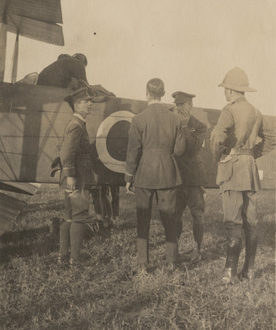 Image: men standing around the tail of a biplane.