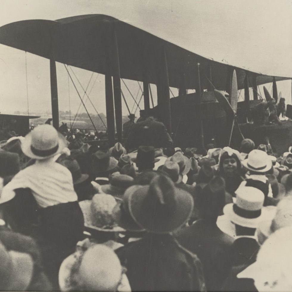 Large biplane surrounded by crowds of people.