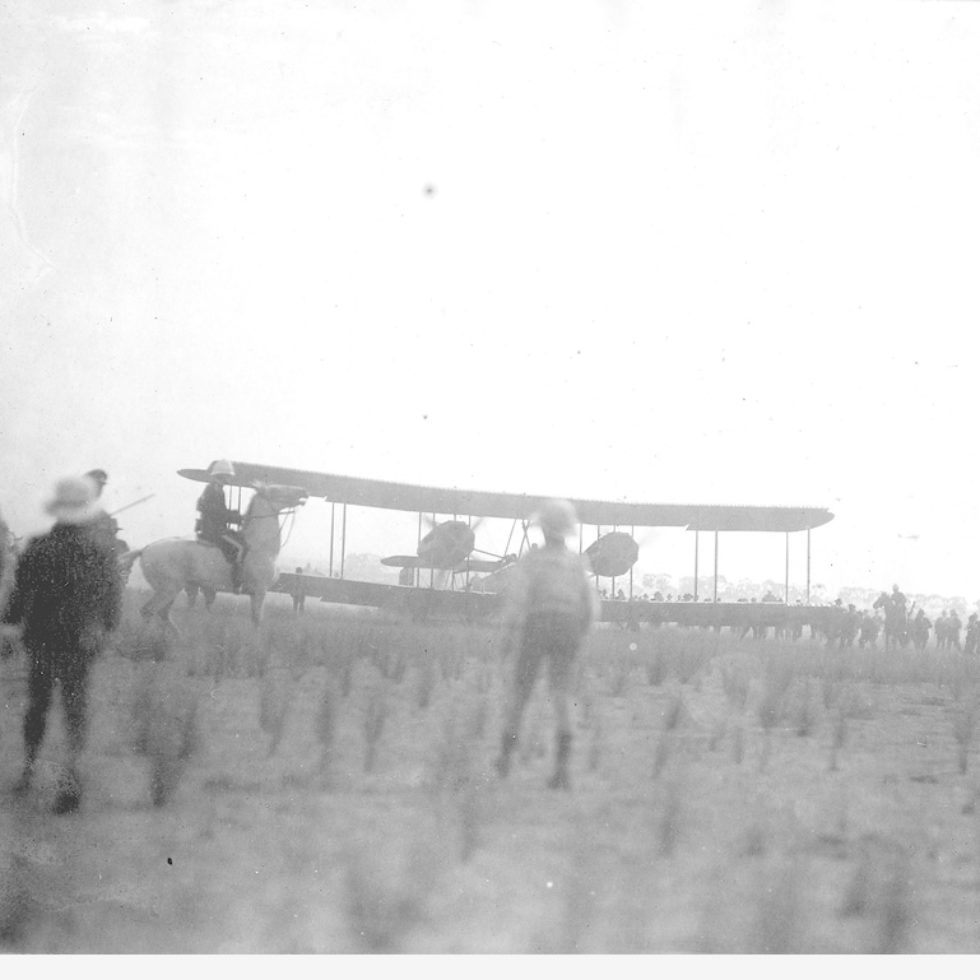 Image: biplane landing with people watching