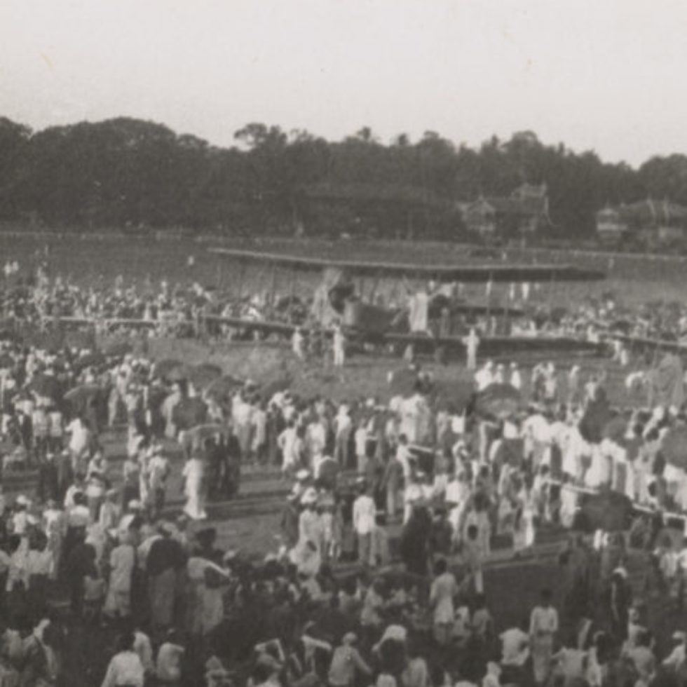 Image: Biplane on open field surrounded by onlookers