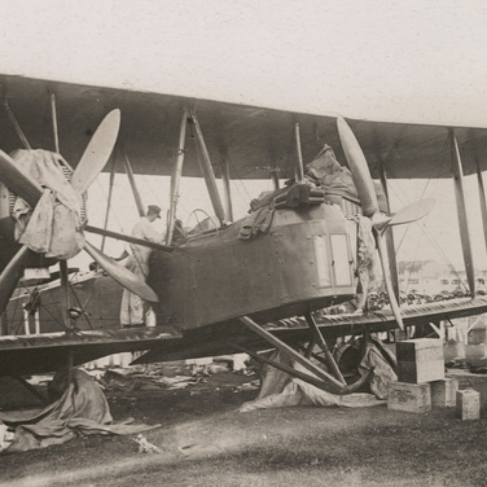 Image: Close up of Biplane with rags covering wheels and the engines. One of the crew is looking into the cockpit from the wing.