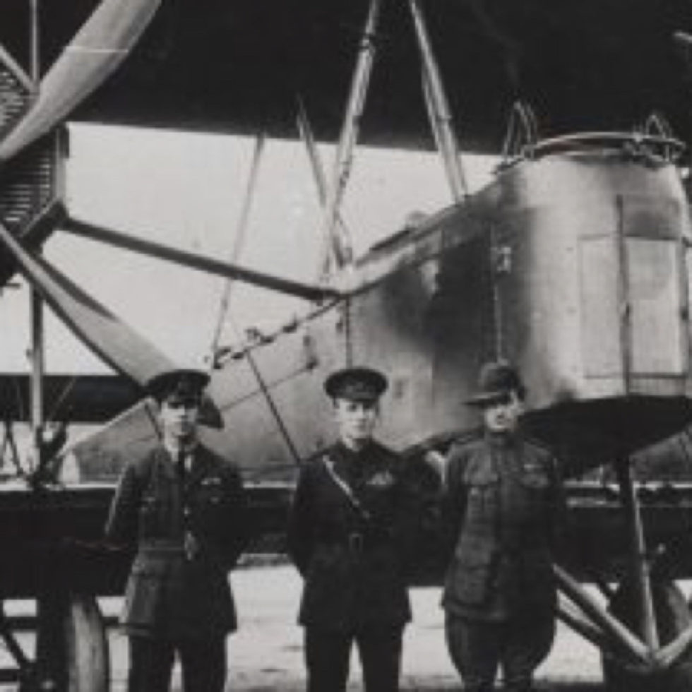 Four flight crew members standing in front of the large bi-plane
